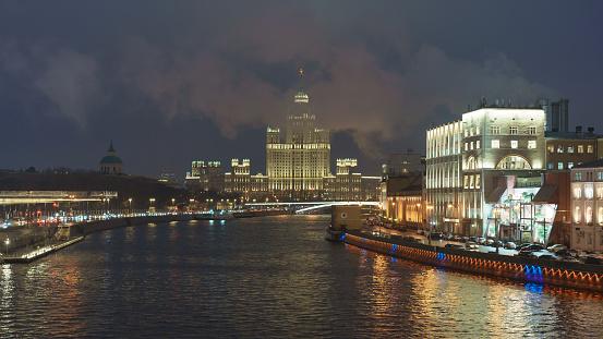 Moscow, Russia - November 19, 2020: Stalinist skyscraper on Kotelnicheskaya embankment, Bolshoy (Big) Ustinsky Bridge. Big traffic. Motorway is filled out by cars. Observation deck in Zaryadye Park