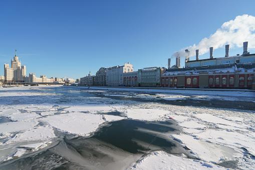 Moscow cityscape in winter sunny day. Stalinist skyscraper, Moskva river had been covered by ice floes. Kotelnicheskaya emb.Thermal Power Station in Raushskaya embankment. Bolshoy Ustinsky Bridge.