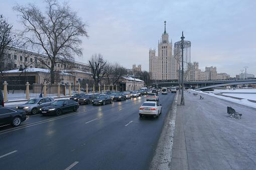 Moscow, Russia - February 19, 2021: Cityscape. Stalinist skyscraper on Kotelnicheskaya embankment, Bolshoy Ustinsky Bridge. Big traffic during coronavirus pandemic. Motorway is filled out by cars