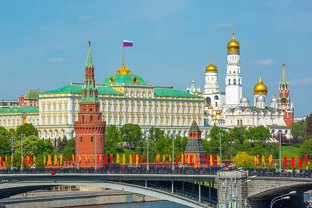 Moscow Kremlin and Bolshoy Kamenny Bridge View of Moscow Kremlin behind the Bolshoy Kamenny Bridge with bright flags kremlin stock pictures, royalty-free photos & images