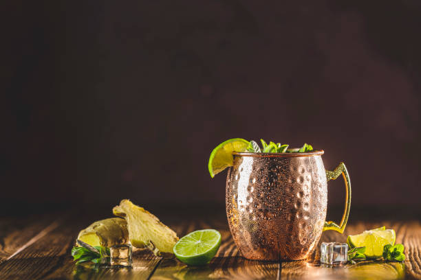 Moscow mule alcoholic cocktail in copper mug with crushed ice, mint and lemon over minton dark wooden table with amazing backlight, copy space. Close up view, copy space stock photo