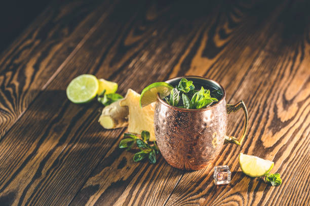 Moscow mule alcoholic cocktail in copper mug with crushed ice, mint and lemon over minton dark wooden table with amazing backlight, copy space stock photo
