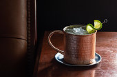 A Moscow Mule cocktail in a copper mug with crushed ice and a lime garnish on a dark wood table next to a leather seat. This drink is made with vodka, ginger beer (or ginger ale), and lime juice. Taken in a dark luxurious bar or restaurant.