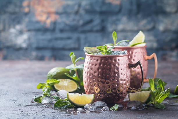 Moscow mule cocktail Moscow mule cocktail in copper cup with lime, ginger beer, vodka and mint garnish moscow russia stock pictures, royalty-free photos & images