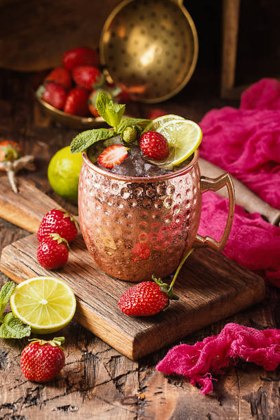 Moscow mule cocktail Moscow mule cocktail in copper cup with lime, strawberry, ginger beer, vodka and mint mule stock pictures, royalty-free photos & images