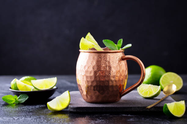 Moscow Mule cocktail with ginger beer, vodka, lime and mint. Dark background. Close up. stock photo
