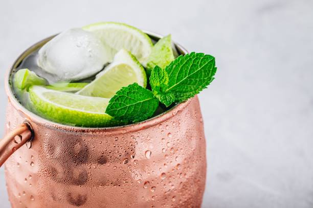 Moscow mule ice cold cocktail in copper cup with lime and and mint on gray stone background Moscow mule ice cold cocktail in copper cup with lime and and mint on gray stone background, copy space. mule stock pictures, royalty-free photos & images