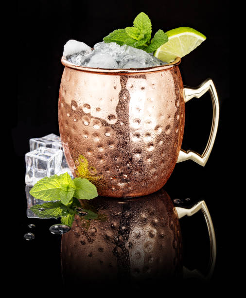 Moscow Mule in a copper cup on black background frosty Moscow Mule in a copper cup isolated on black background mule stock pictures, royalty-free photos & images