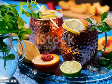 Moscow mule cocktail with fresh peaches and lemon balm