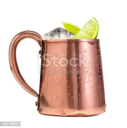 A Moscow mule drink in a copper cup on a white background.  Moscow mules are made with vodka, ginger beer, and lime and served over ice in a copper mug.