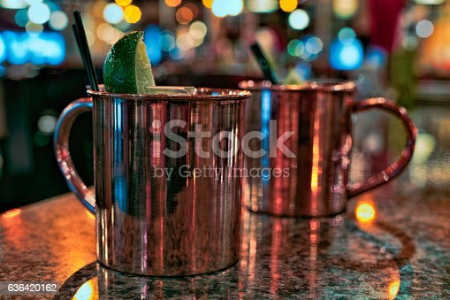 Two Moscow Mule cocktails in copper mugs on a marble table in a bar. The drinks are garnished with black straws and a lime.