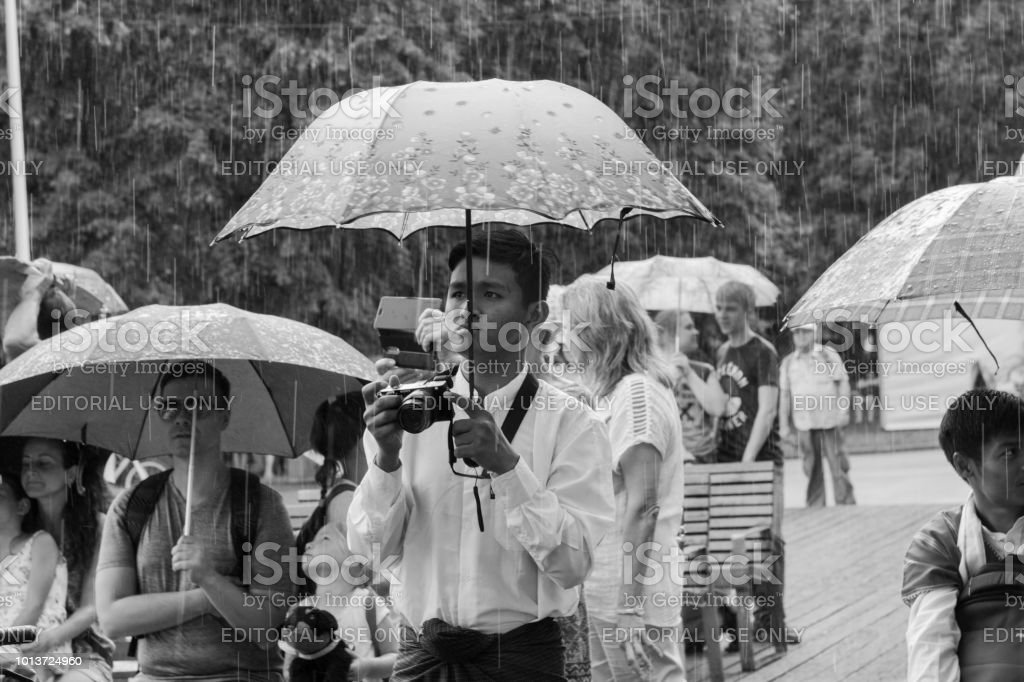 Moscow, Russia, 04 august 2018 Unknown Balinese young guys hiding from the rain under an umbrella at the festival of Indonesia stock photo