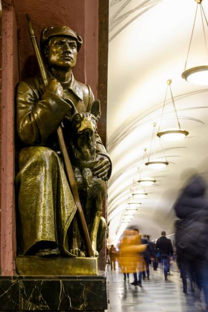 moskau, russland - 16. november 2017: moskauer u-bahn station platz der revolution. bronzeskulptur von sowjetischen soldaten mit hund - hundeplätze stock-fotos und bilder