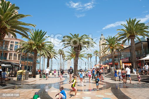 Adelaide, Australia - January 09, 2016: Children playing in the water feature at Moseley Square, Glenelg. Glenelg is the very popular seaside suburb of Adelaide, South Australia. On warm days tourists and locals flock to the area for shopping, entertainment and the beach.