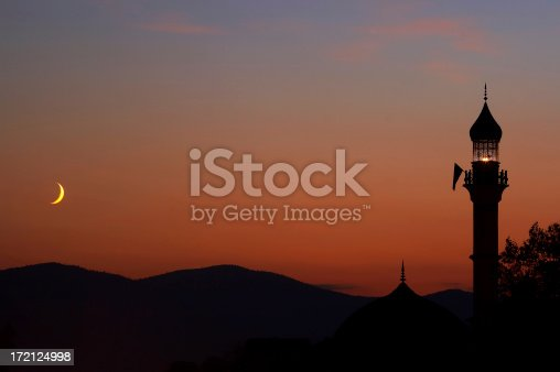 Mosque at dusk with crescent moon
