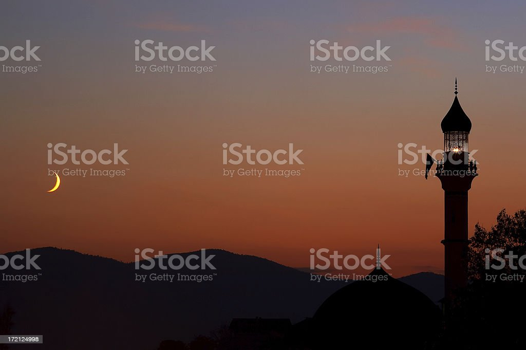 Mosque at dusk with crescent moon stock photo