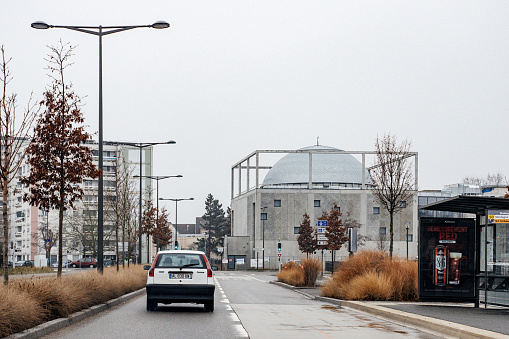 Paris, France - Feb 4, 2019: Driver POV personal perspective at the street with Mosque Hautepierre Strasbourg - lonely car on the road