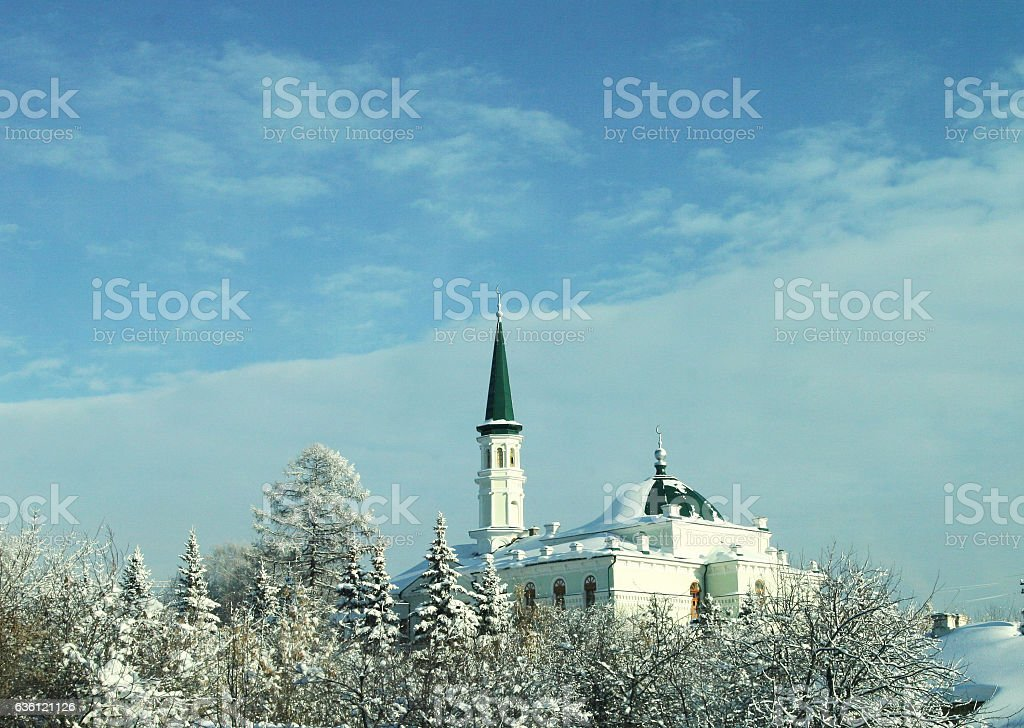 Mosque with a green spire in the winter sky stock photo