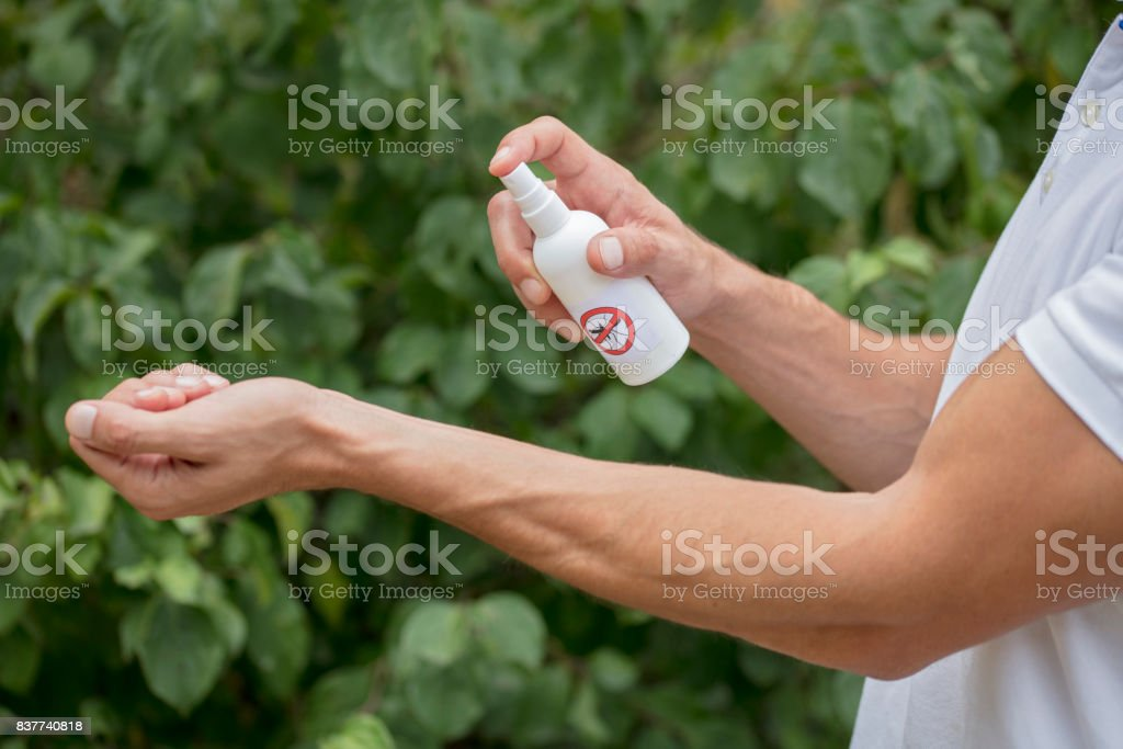 Mosquito repellent. Man using insect repellent spray outdoors. stock photo