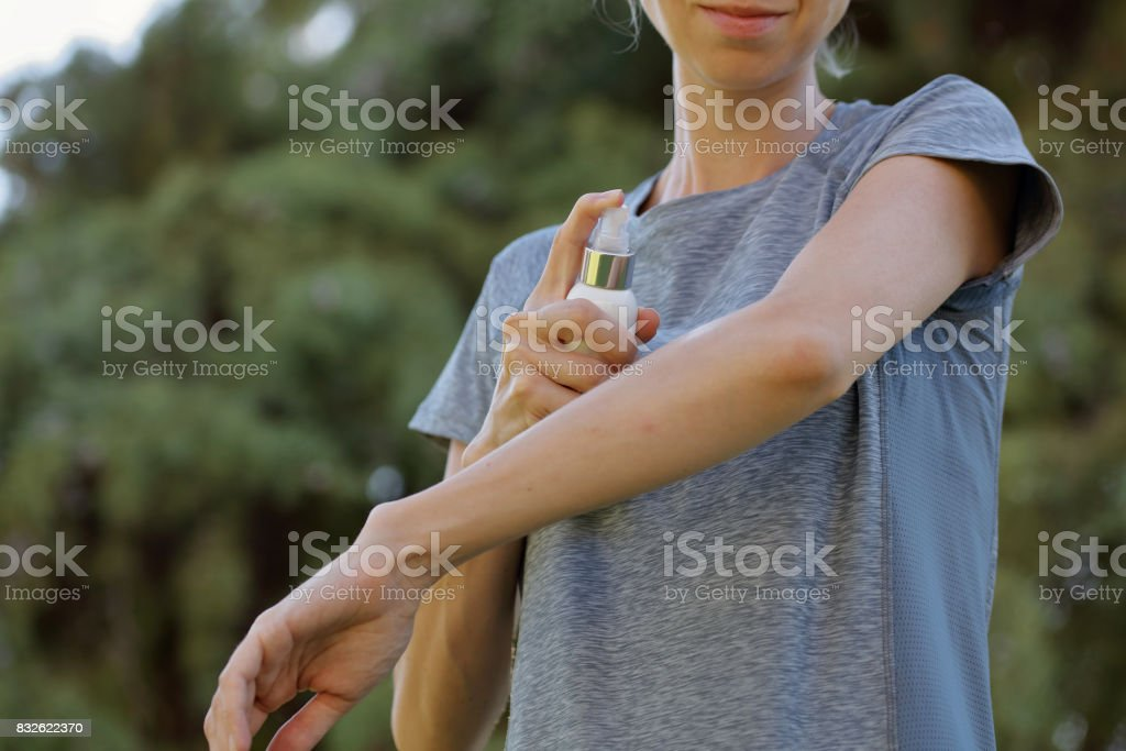 Mosquito repellent. Woman using insect repellent cream outdoors. stock photo