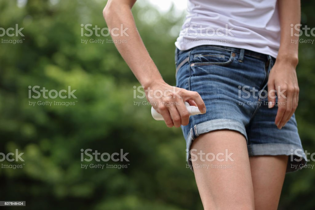 Mosquito repellent. Woman using insect repellent spray outdoors. stock photo