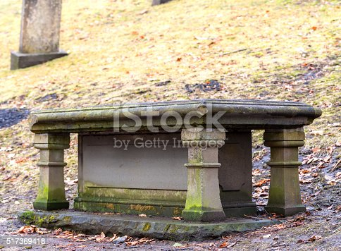 An old moss covered grave crypt at the bottom of a hill. Focus is on the closest corner. There is room for text above.