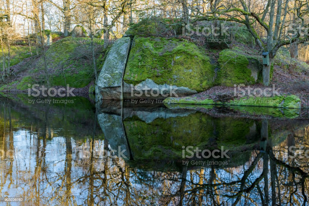 Moss covered riverside rock stock photo