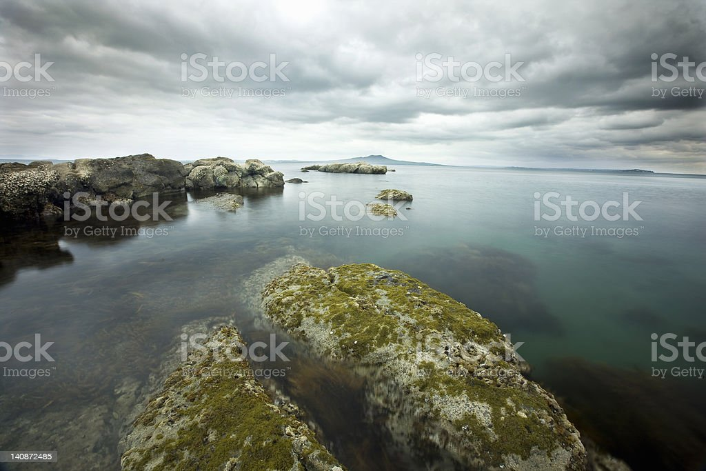 Moss-covered rocks on coastline stock photo