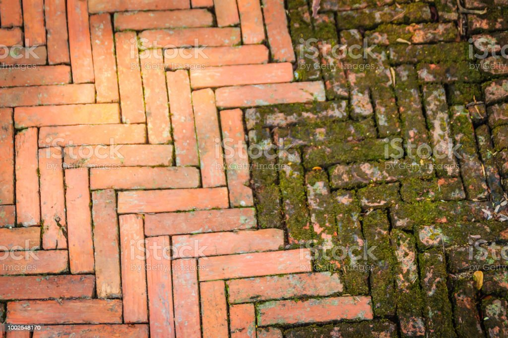 Mossy diagonal pattern of brick pavement in a herringbone style for background, Old orange bricks tiled floor with zigzag pattern. Old peeling chevron zigzag diagonal brickwork texture background. stock photo