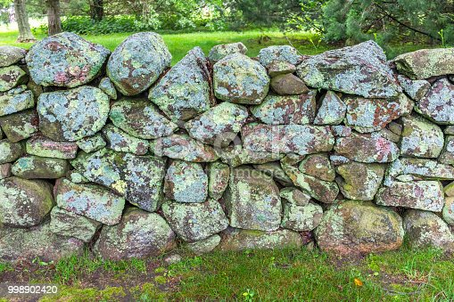 Green Mossy Old Stone Wall New England Padanaram Dartmouth Massachusetts. Stone walls were built in the early 1600s and 1700s in New England to mark property lines.