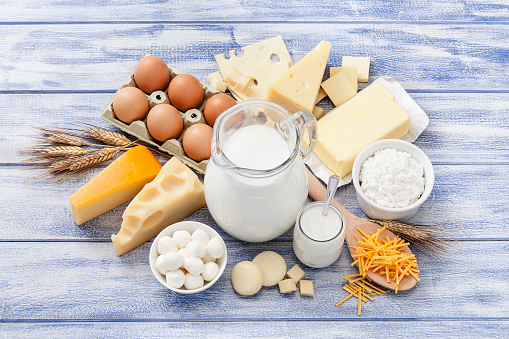 Top view of most common dairy products shot on blue striped table. Dairy products included in the composition are milk, various cheeses, yogurt, cottage cheese, butter and eggs. Predominant colors are white, blue and yellow. High key DSRL studio photo taken with Canon EOS 5D Mk II and Canon EF 100mm f/2.8L Macro IS USM.