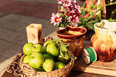 Close up of a basket filled with green apples, placed on the wooden table with some ceramic vases and small flower vase next to it.