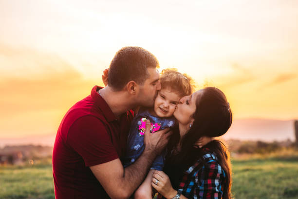 Most safe place on the world Cute little girl between her young caucasian parents getting kisses. little girl kissing dad on cheek stock pictures, royalty-free photos & images