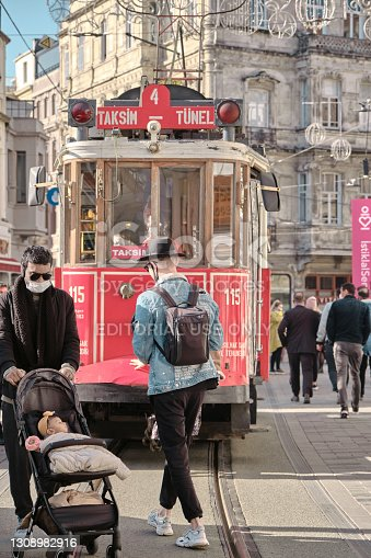 Turkey istanbul 04.03.2021. Most well known taksim square during morning with red, vintage and retro style tram in istiklal avenue and many tourists with medical masks.