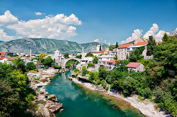 "Mostar, Bosnia and Hercegovina ""Old Arc bridge in Mostar, Bosnia and Hercegovina. Destroyed during the war. It was then rebuild after the war. Beautiful cityscape of Mostar, visible are traditional architecture of Bosnia, many green trees and cumulus clouds over Neretva River.See more images like this in:"" bosnia and hercegovina stock pictures, royalty-free photos & images"