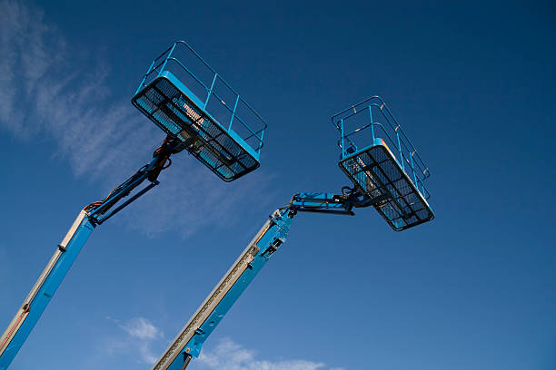 Mostly Blue Two blue cherry picker lifts against a blue sky mobile crane stock pictures, royalty-free photos & images