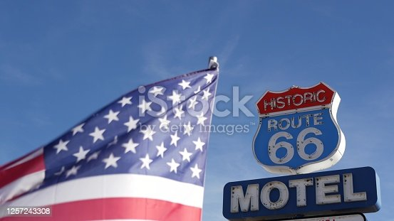 Motel retro sign on historic route 66 famous travel destination, vintage symbol of road trip in USA. Iconic lodging signboard in Arizona desert. Old-fashioned neon signage. National state flag waving.