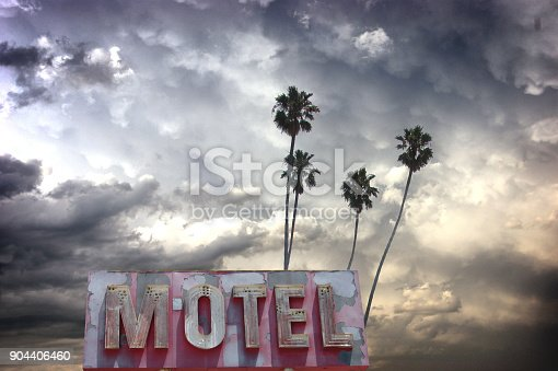 aged and worn motel sign with palm tree and stormy sky