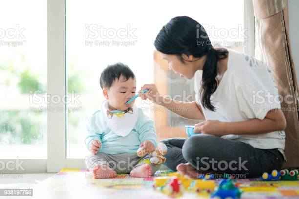 Mothe feed a baby by blue spoon in family room picture id938197766?b=1&k=6&m=938197766&s=612x612&h= kotqhgxjstbbzmooawunv97zs213lnba1tzie7t6s0=