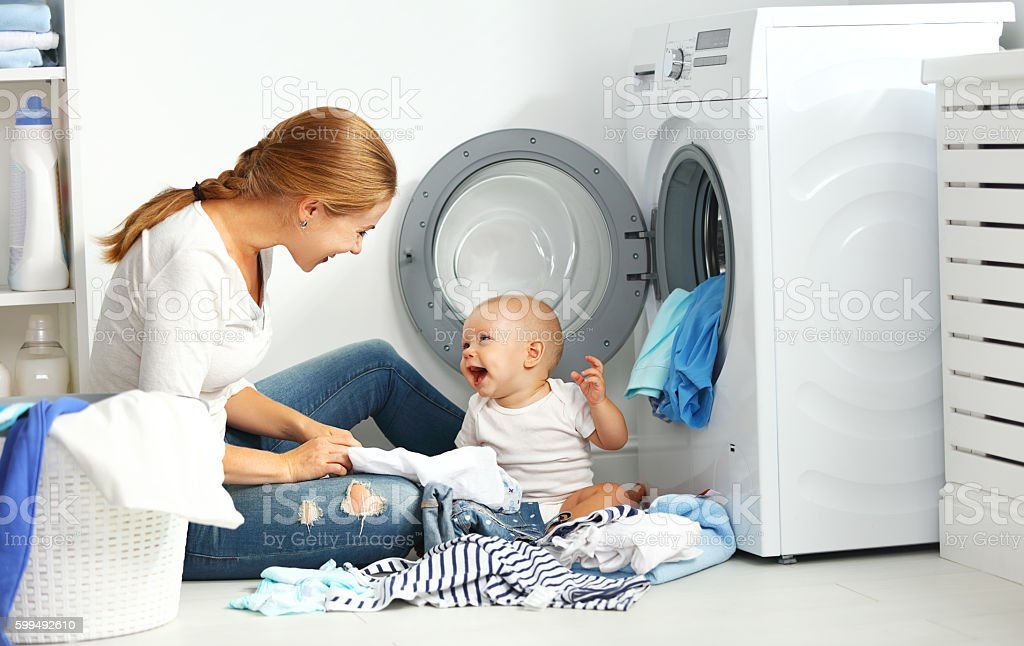mother a housewife with a baby  fold clothes into washing - foto de stock