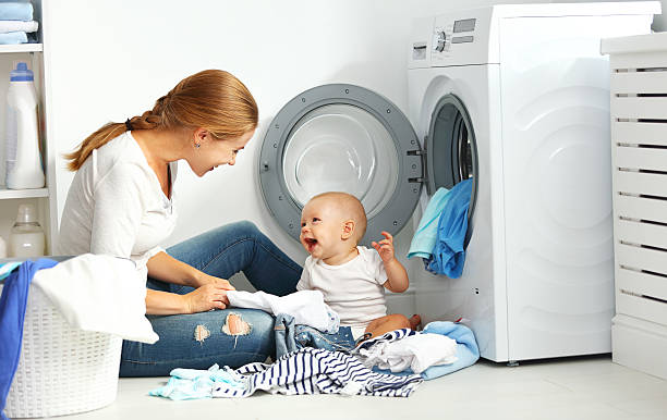 mother a housewife with a baby  fold clothes into washing - dona de casa - fotografias e filmes do acervo