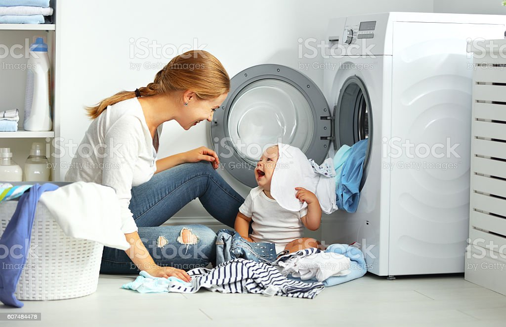 mother a housewife with a baby engaged in laundry fold clothes into...