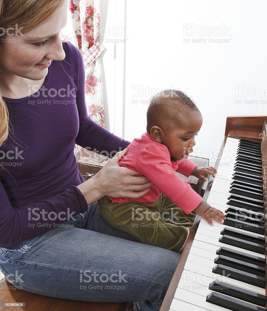 mother, adopted baby african descent multi-ethnic daughter playing piano stock photo