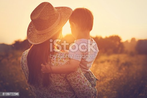 istock Mother and a baby enjoying beautiful sunset 515972296