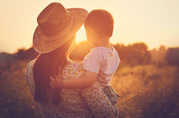 Mutter und ihr Baby genießen Sie den wunderschönen Sonnenuntergang – Foto
