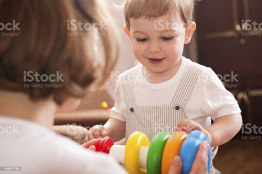 Mother and a child playing with a colorful baby toy royalty-free stock photo