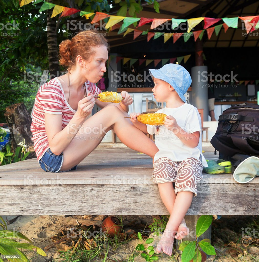mother and a son eating corn outdoors stock photo
