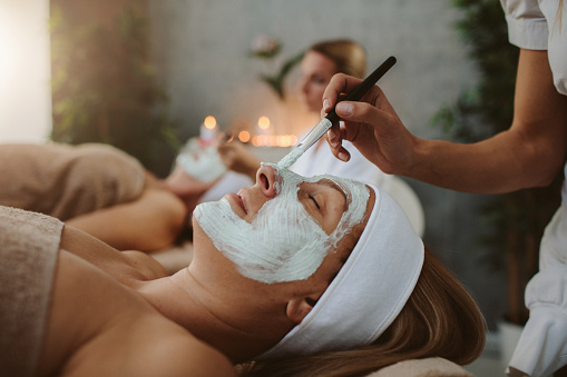 Beauty treatment. Beauticians applying facial mask on mature adult and senior women's face.