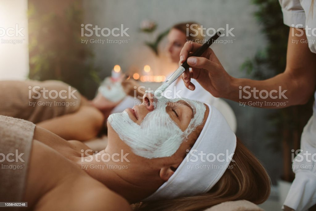 Mother and adult daughter enjoy beauty treatment in a spa center stock photo