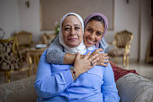Muslim senior mother and her adult daughter hugging in the living room.